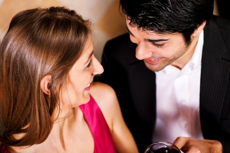 Young couple - man and woman - in a restaurant clinking the red wine glasses; focus on the glasses photo