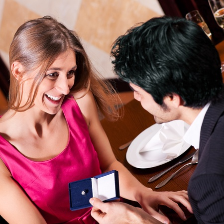 Young man making a wedding proposal offering a ring to his girlfriend in a fancy restaurant photo