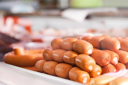 Varieties of fresh sausages for sale in a butcher shop photo