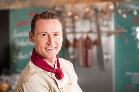 Portrait of handsome butcher smiling while looking at you