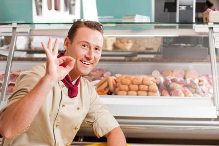 carniceria: Carnicero feliz que muestra signo bien con variedad de carnes frescas en el fondo Foto de archivo
