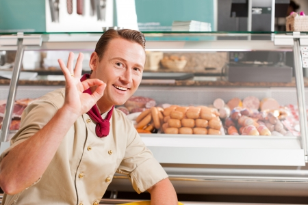 butchery: Happy butcher showing okay sign with variety of fresh meat in background Stock Photo