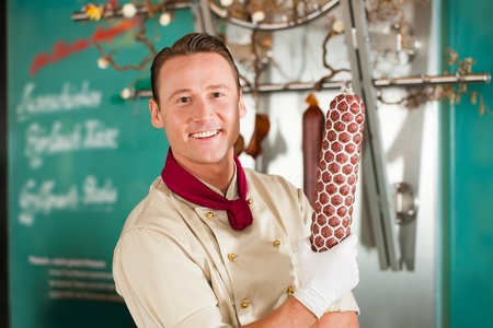 Smiling butcher showing fresh smoked sausage at his shop photo