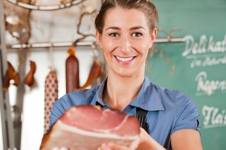 flesh: Portrait of pretty female butcher smiling while holding raw meat