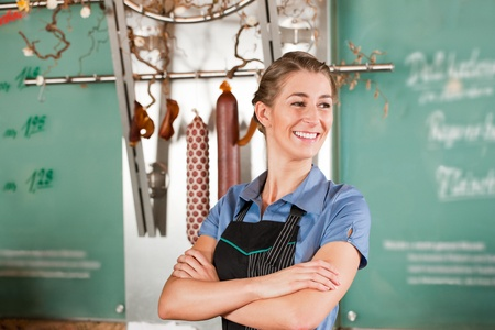 selling service: Confident female butcher smiling with arms crossed at butchery