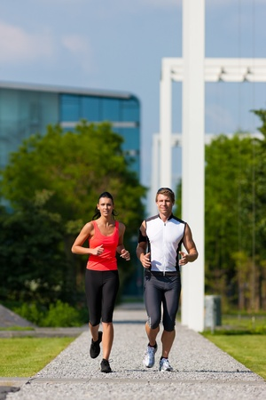 Urban sports - couple jogging for fitness in the city on a beautiful summer day Stock Photo - 12443219