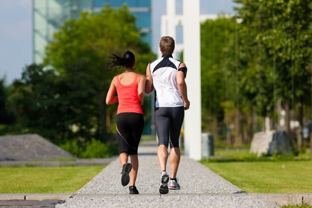 work life balance: Urban sports - couple jogging for fitness in the city on a beautiful summer day Stock Photo