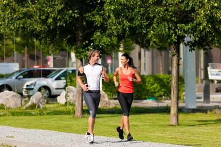 Urban sports - couple jogging for fitness in the city on a beautiful summer day photo