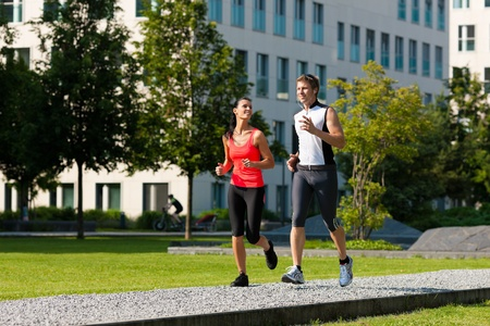 city life: Urban sports - couple jogging for fitness in the city on a beautiful summer day Stock Photo