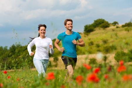 sportive: Young fitness couple doing sports outdoors; jogging on a green meadow in summer under a blue sky