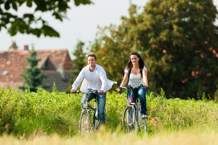 Happy young couple - man and woman - cycling in summer in nature photo