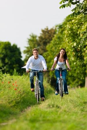 moto da cross: Felice giovane coppia - uomo e donna - in bicicletta in estate nella natura Archivio Fotografico