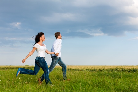 Happy couple running on a dirt road in summer holding hands photo
