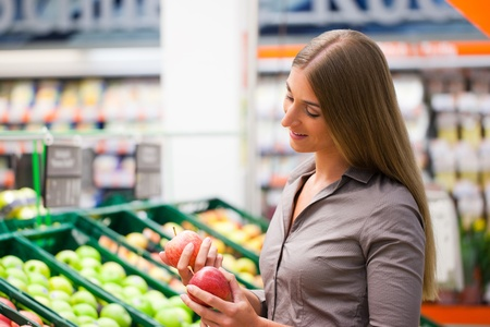 Beautiful female customer selecting apples at supermarket Stock Photo - 12388911