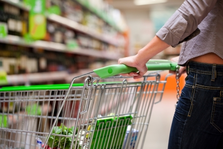shopping trolleys: Cropped image of female shopper with cart at supermarket