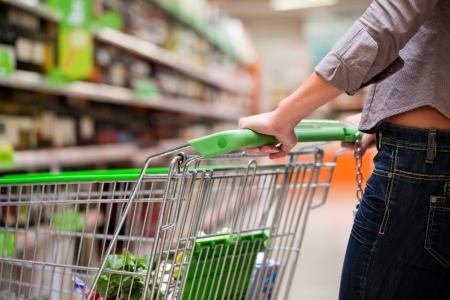 carro supermercado: Imagen recortada de los compradores mujer con carrito en el supermercado