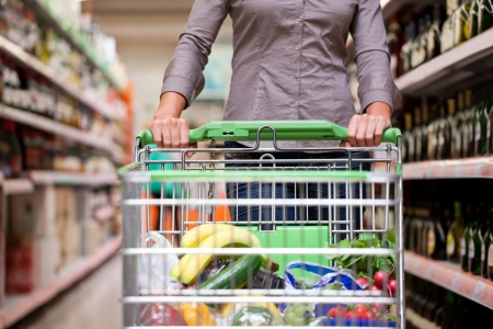 Female customer shopping at supermarket with trolley Stock Photo
