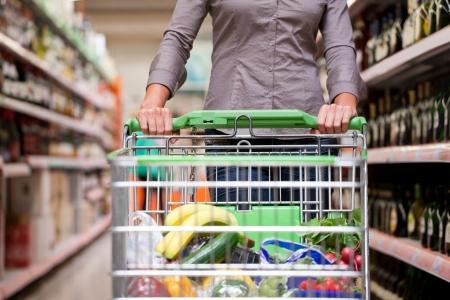 carro supermercado: Mujer de compra del cliente en el supermercado con el carro Foto de archivo