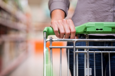 Closeup of female shopper with trolley at supermarket photo
