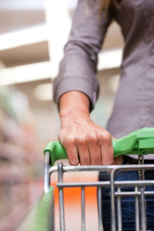 cropped image: Cropped image of woman holding pushcart at supermarket
