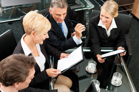 Business - meeting in an office; the businesspeople are discussing a project photo