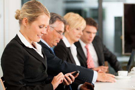 Business - team in an office; the junior manager is checking mails Stock Photo - 12443272