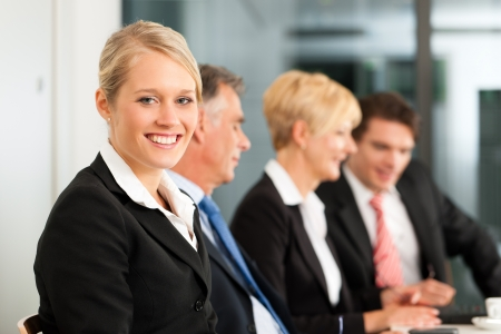 junior: Business - team in an office; a woman is looking into the camera