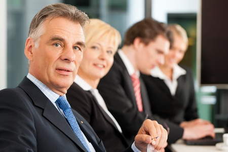 Business - team in an office; the boss is looking into the camera Stock Photo - 12443273