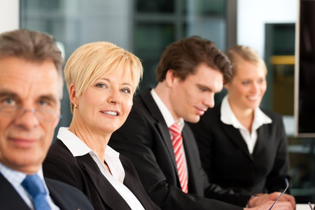 Business - team in an office; the boss is looking into the camera photo