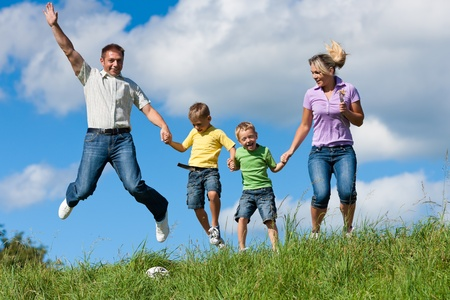family health: Happy family with children jumping in a meadow in summer Stock Photo