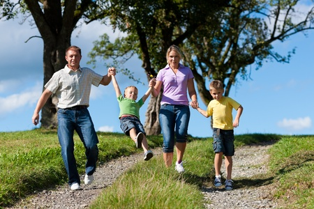 Happy family outdoors is running on a dirt path on a beautiful summer day photo