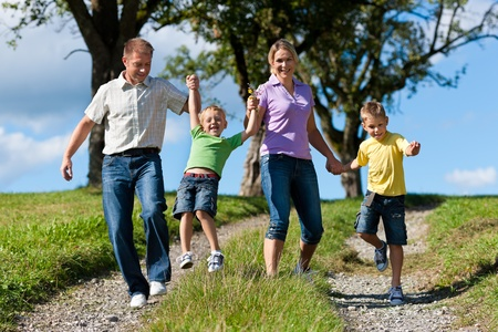 Happy family outdoors is running on a dirt path on a beautiful summer day Stock Photo - 12443344