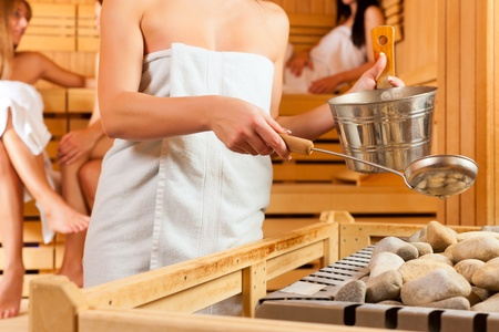 steam bath: Wellness - young happy women in sauna of a Spa, water and scent are splashed on hot stones for steam