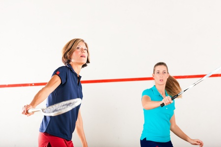 racket sport: Dos mujeres jugando al squash como deporte de la raqueta en el gimnasio, puede que sea una competencia Foto de archivo