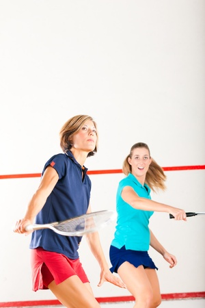 Two women playing squash as racket sport in gym, it might be a competition photo