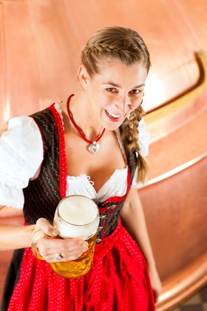 Woman in Bavarian Tracht, a female brewer, with beer stein in brewery photo