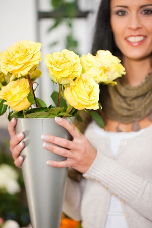 yellow roses: Female florist in flower shop or nursery presenting yellow roses