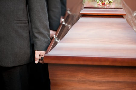 Religion, death and dolor  - coffin bearer carrying casket at funeral to cemetery Stock Photo - 12443381