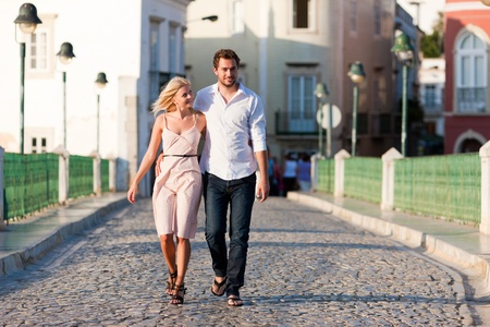 Couple having a city break in summer walking on a bridge over a river in the evening light   photo