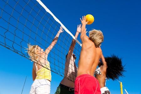 pelota de voleibol: Los jugadores practicar deportes de verano tratando de bloquear a un peligroso ataque en un partido de voleibol de playa