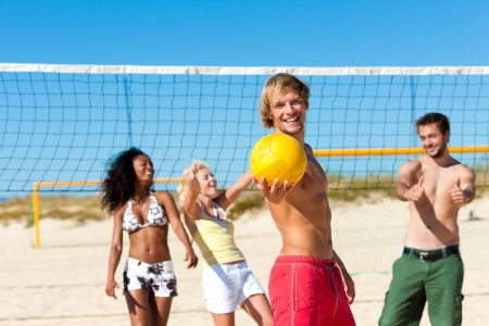 beach front: Group of friends - women and men - playing beach volleyball, one in front having the ball Stock Photo