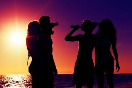 shining through: Persone due coppie sulla spiaggia una festa, bere e avere un sacco di divertimento nel tramonto solo silhouette di persone da vedere, persone con bottiglie in mano con il sole che splende attraverso Archivio Fotografico