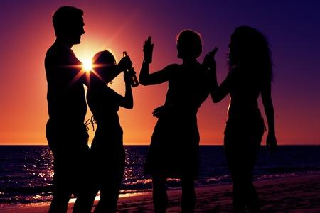hombre tomando cerveza: Las personas dos parejas en la playa a tener una fiesta, beber y tener un mont�n de diversi�n en la puesta del sol s�lo la silueta de las personas que se ven, las personas que tengan botellas en sus manos con el sol brillando a trav�s de