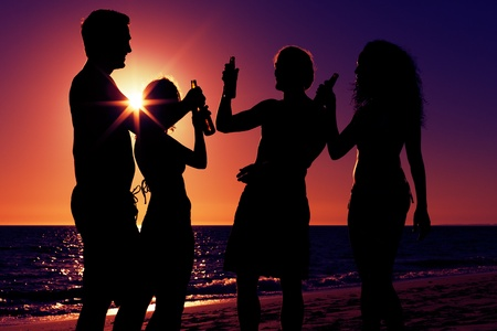 girl drinking: People  two couples  on the beach having a party, drinking and having a lot of fun in the sunset  only silhouette of people to be seen, people having bottles in their hands with the sun shining through  Stock Photo