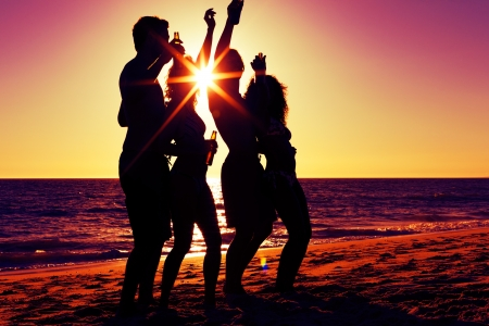friends party: People  two couples  on the beach having a party, drinking and having a lot of fun in the sunset  only silhouette of people to be seen, people having bottles in their hands with the sun shining through  Stock Photo