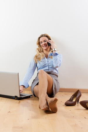 telecommuter: Business woman working at home with her laptop on the floor and makes a phone call