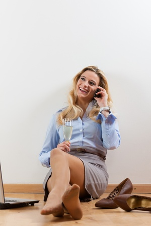 Business woman working at home with her laptop on the floor and makes a phone call photo