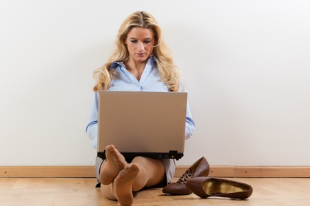 telecommuting: Business woman working at home with her laptop on the floor