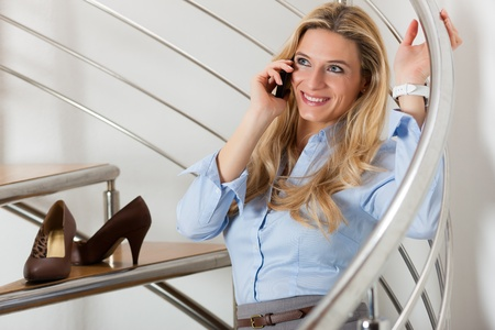 closing time: Businesswoman making a phone call and sitting on the stairs in her apartment Stock Photo