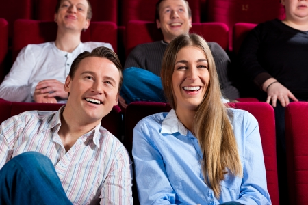 theater audience: Couple and other people, probably friends, in cinema watching a movie; it seems to be a funny movie